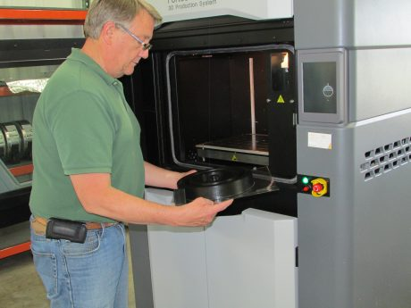 Scott Fortune removes a part from Upper Iowa's new #-D printer.